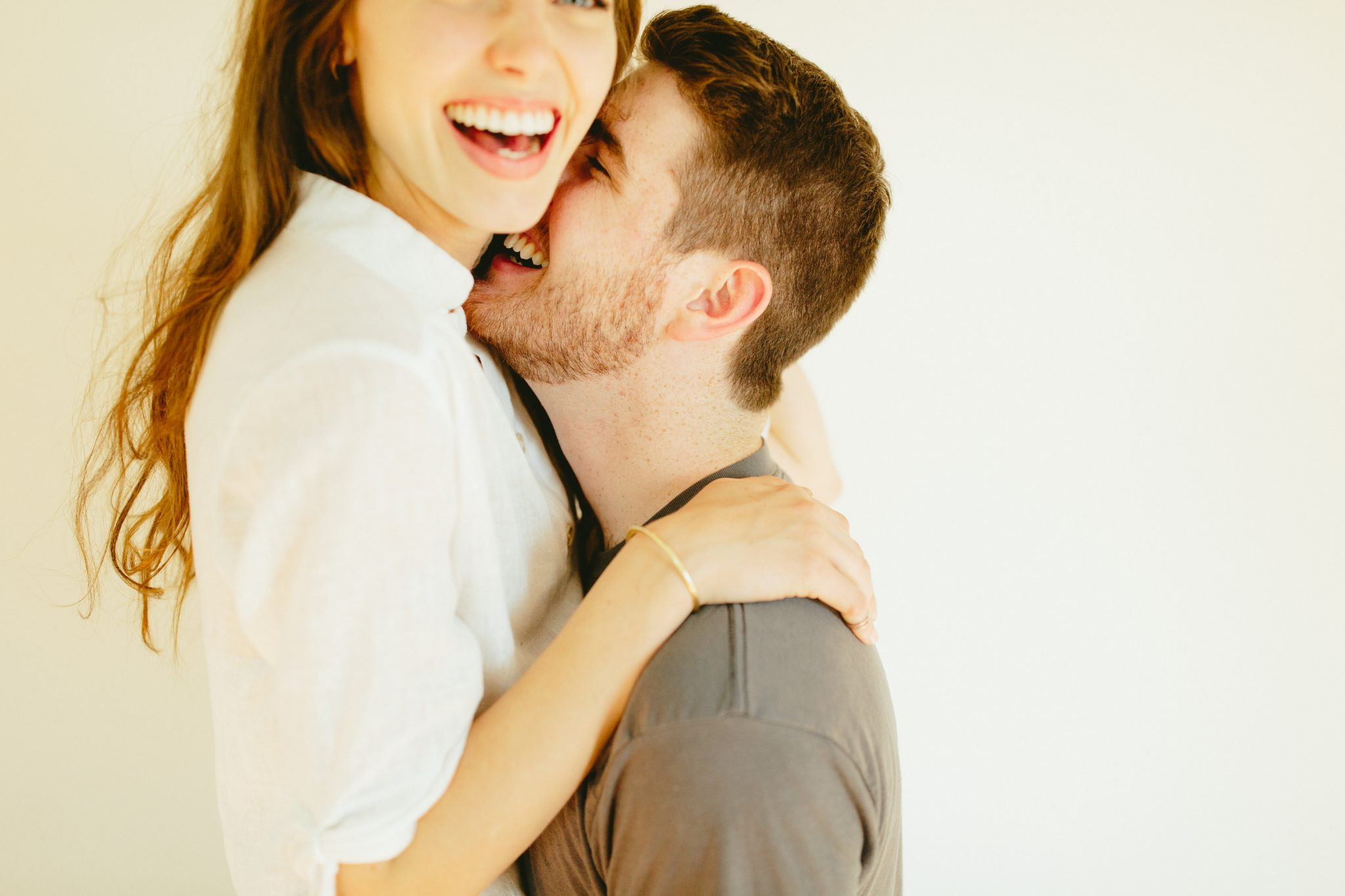 Engaged Lancaster couple laughing in studio