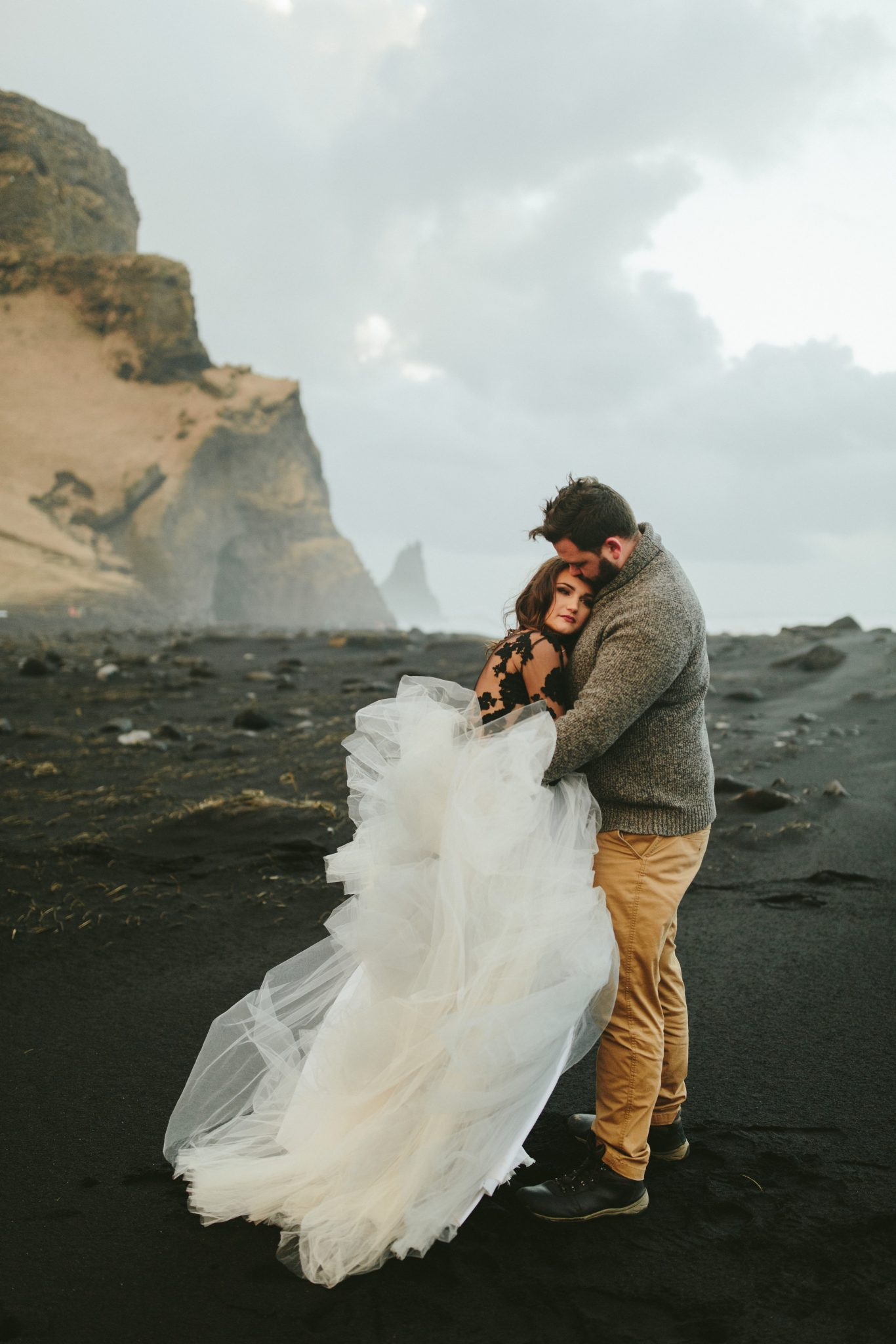 black sand beach photos, iceland black sand beach, see through wedding dress, couples photos in iceland,brooklyn wedding photographer, Iceland wedding photos, brooklyn new york photographer, destination wedding photographer, photojournalistic brooklyn wedding photographer, philadelphia wedding photographer, photojournalistic philadelphia wedding photographer, unique wedding photos, untraditional wedding ideas, Iceland elopement photographer, destination elopement photographer, unique elopement inspiration. Tulle wedding skirt, black wedding dress